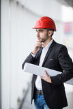 Man in hard hats at building with plans thinking Stock Photo