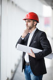 Man in hard hats at building with plans thinking Royalty Free Stock Photo