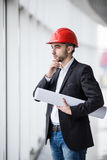 Man in hard hats at building with plans thinking royalty free stock photography