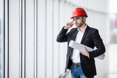 Man in hard hats at building with plans thinking Stock Photography