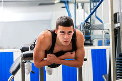 Man hard working his  back on hyperextension bench. Royalty Free Stock Images