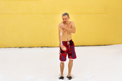 Man hardening in winter season. Portrait full length of young man wearing red shorts with bare torso, wiping snow in the winter, male promoting health. Hardening Royalty Free Stock Photography
