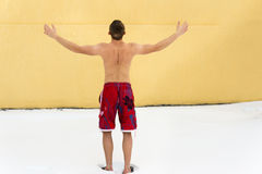Man hardening in winter season. Sports guy without clothing in winter snow. Hardening in winter season. Frosty weather. Yellow wall on background Royalty Free Stock Photo