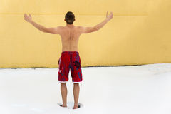 Man hardening in winter season. Sports guy without clothing in winter snow. Hardening in winter season. Frosty weather. Yellow wall on background Stock Images
