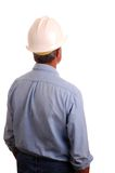 Man in hardhat. Man in blue jeans and work shirt wearing a hardhat seen from behind looking into distance - isolated over white Stock Images