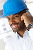 Man in hardhat on call. Closeup portrait of smiling ethnic engineer in hardhat on phone call Stock Photo