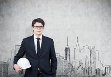Man in hardhat and glasses, concrete wall, city Stock Photo