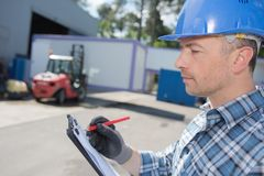 Man in hardhat making notes on clipboard. Man Royalty Free Stock Photos