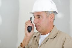 Man with hardhat and walky talky radio at construction site. Man royalty free stock photography