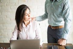 Man harrasing a woman at work Royalty Free Stock Photo