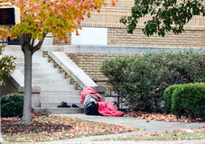 Homeless man lying down outside Stock Photo