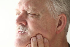 Man has bad tooth or jaw pain. Senior man shows area of pain on his jaw with his fingers royalty free stock photos