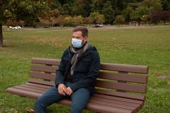Man has cold or flu. Man has catch cold. Man has cold or flu.  Man has catch cold is sitting on bench in the park Royalty Free Stock Photography