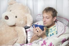 A man has a cold. A man lying in bed with medication and a thermometer. Runny nose,sore throat stock photo