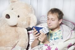 A man has a cold. A man lying in bed with medication and a thermometer. Runny nose,sore throat stock photography