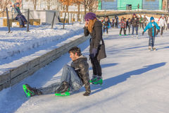 A man has hurt himself while ice skating. A man has fell and hurt himself while ice skating, and a girl is trying to help him while talking on the phone in a royalty free stock photography