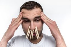 Man has a headache and his nose is running. He has an allergy. He is suffering from that. Man`s nose is closed with stock photography