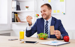Man has healthy business lunch in modern office interior Stock Photography
