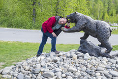 Man Has His Head in the Jaw of a Bear Statue Royalty Free Stock Photo