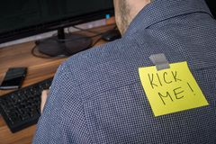 Man has note with Kick me written on it. Joke on first april.  Royalty Free Stock Images