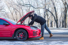Man has problems with the car on winter road. Man in trouble with his broken car .He  is looking at engine under hood Stock Photos
