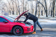 Man has problems with the car on winter road. Man in trouble with his broken car .He is worried, he is looking at engine under hood Stock Photos