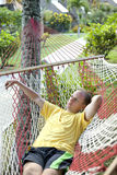 Man has a rest in a hammock in a surrounding of the tropical nature Royalty Free Stock Image