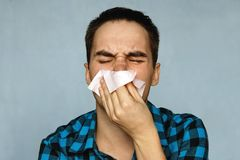 The man has a runny nose. The person with a cold sneezes into a handkerchief. Snot coming out of nose stock images