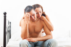 Man has sad face, woman consoling him on bed in bedroom Royalty Free Stock Images