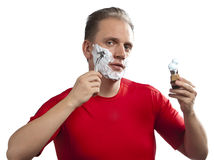 Man has a shave- with the razor and a small brush Stock Images