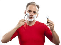 Man has a shave- with the razor and a small brush Royalty Free Stock Photos