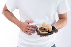 A man has a stomachache after eating delicious zongzirice dumpling on Dragon Boat Festival, Asian traditional food. White background royalty free stock photos