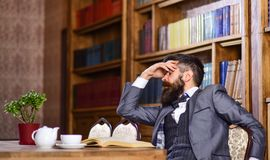 Man has terrible headache. Bearded man in formal suit suffers from negative thoughts and looks unsatisfaied. Mature man with tired face has afternoon tea Stock Photography
