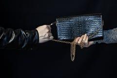 Man hastiga grepp en handväska från händerna av en kvinna, en svart bakgrundsbrottsling arkivfoton