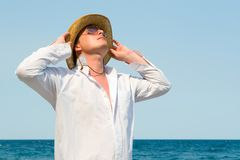 Man with hat on the beach Stock Photos