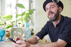 Man with hat and beard happy looking at phone and soap bubbles i Stock Image