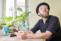 Man with hat and beard happy looking at phone and soap bubbles i Stock Images