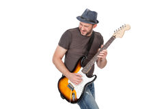 Man with hat and beard play on electric guitar with enthusiasm. Isolated on white Royalty Free Stock Image