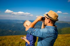 Dangerous journey for a young couple. Man in a hat with a beautiful women are navigating far into the mountains Royalty Free Stock Photography