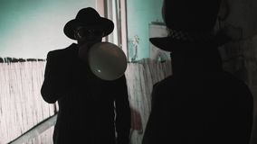 Man in hat blowing up a balloon and talk with man in top hat in low lighted room. Man in suit, hat and sunglusses blowing up a balloon and talk with man in top stock video footage