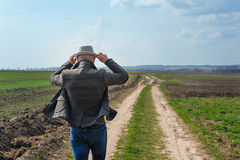 Man in the hat is on the field. back view Royalty Free Stock Photography