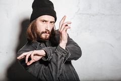 Man in hat gesturing with hands and looking at camera. Portrait of a serious bearded man in hat gesturing with hands and looking at camera  over wall background Stock Photo