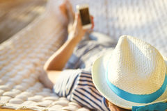 Man in hat in a hammock with mobile phone on a summer day Royalty Free Stock Photo