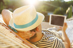 Man in hat in a hammock with tablet computer on a summer day Royalty Free Stock Photo