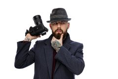 A man in a hat holding dslr camera. Thinking bearded man in a hat holding dslr camera. Isolated on a white background Royalty Free Stock Photo
