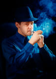 Man with Hat Lighting His Pipe Royalty Free Stock Image