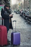 Man carrying his luggage on the street. Man with hat and luggage on the streets of Barcelona Stock Image