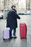 Man carrying his luggage on the street. Man with hat and luggage on the streets of Barcelona Royalty Free Stock Image