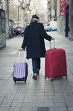 Man carrying his luggage on the street. Man with hat and luggage on the streets of Barcelona Stock Photos