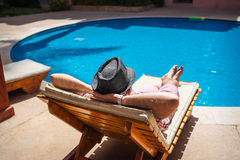 Man in a hat lying on a lounger by the pool Stock Image